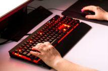 Person, die ein Browsergame mit einer beleuchteten Gaming Tastatur spielt