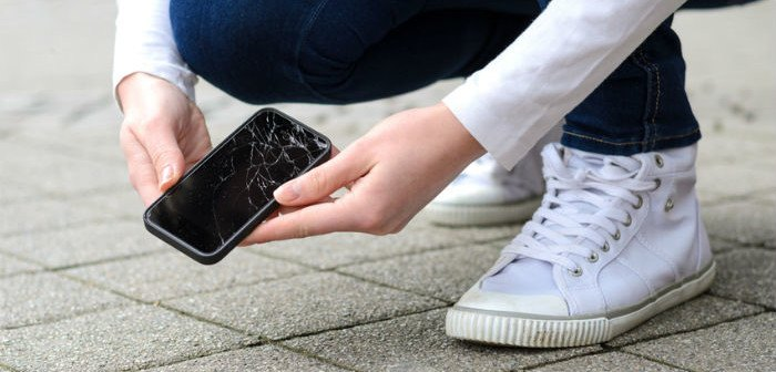 Person hebt kaputtes Handy auf