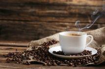 dampfende Kaffeetasse steht auf Kaffeebohnen