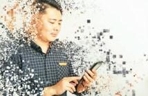Mensch mit Smartphone in der Hand umgeben von fliegenden Pixeln