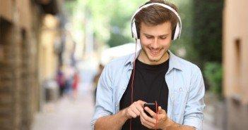 Mann benutzt Prepaidhandy mit mp3 Player