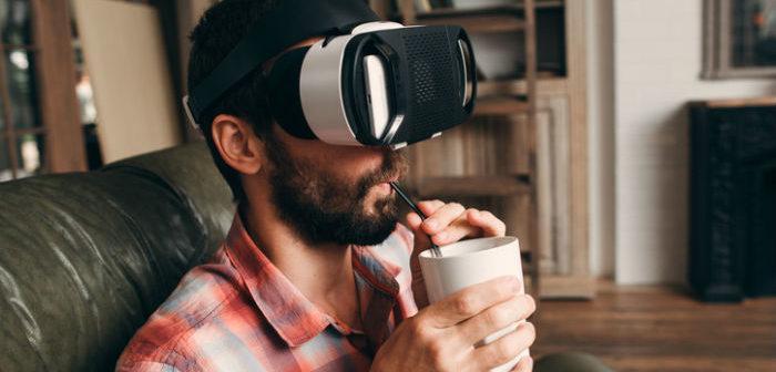 Mann mit einer Virtual Reality Brille auf dem Sofa