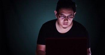 Männlicher Aisate arbeitet an einem Laptop in einem dunklen Raum