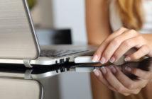 Frau steckt Surfstick in Laptop