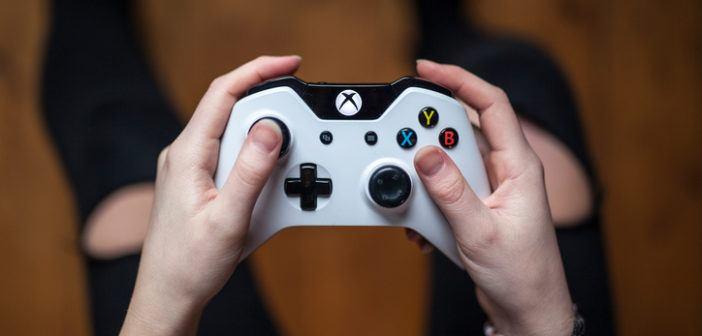 Draufsicht, wie ein Mann einen weißen XBox-Controller hält