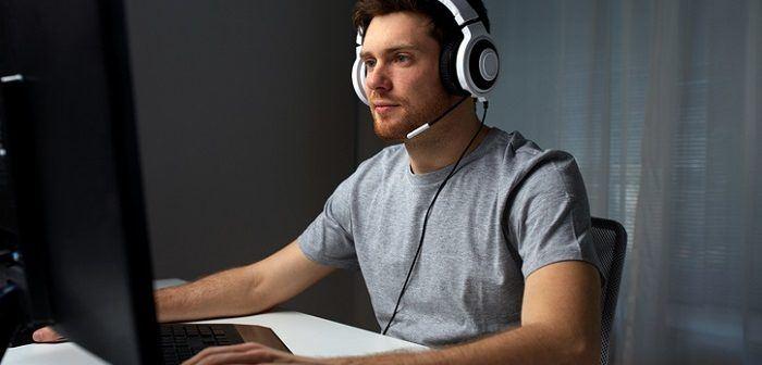 Mann sitzt vor PC mit Headset und spielt augenscheinlich ein Computerspiel