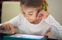 Kind programmiert Lernroboter am Tablet