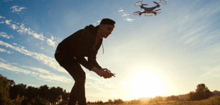 Junge steuert eine Drohne im Sonnenschein