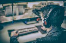 Mann sitzt vor PC-Monitoren und spielt Call of Duty WW2