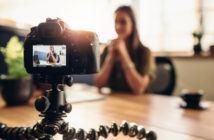 Frau filmt sich mit einer DSLR Kamera