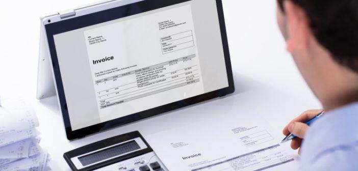 Ein Mann schreibt am PC Rechnungen