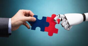 Menschliche Hand reicht einem Roboter die Hand