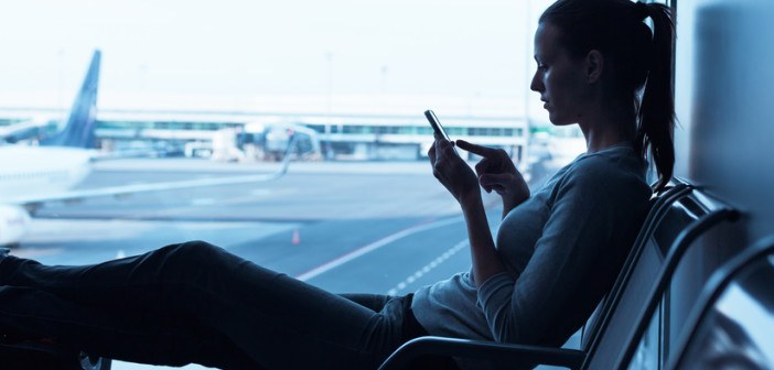 Frau mit Smartphone am Flughafen
