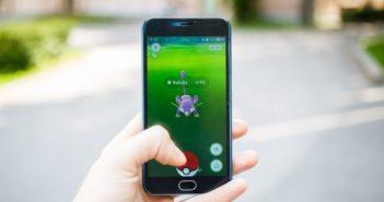 Im Vordergrund eine Hand mit einem Smartphone auf dem die App Pokemon Go läuft. Hintergrund unscharf, eine Straße ist erkennbar.