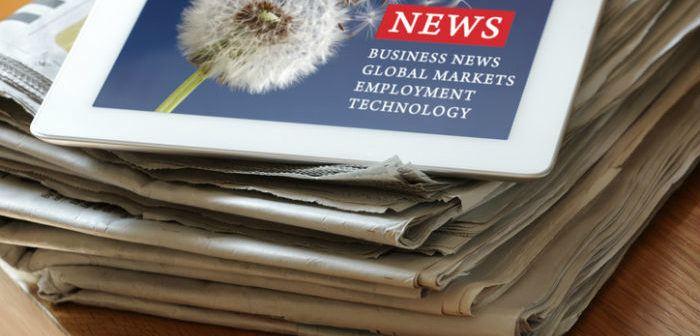 Stapel Zeitungen und ein Tablet mit Nachrichten