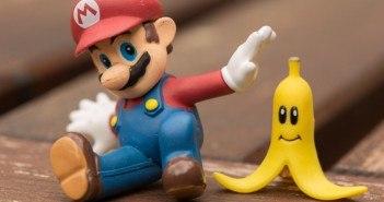 Mario sitzt mit einer Banane mit Gesicht auf einem Holzuntergrund